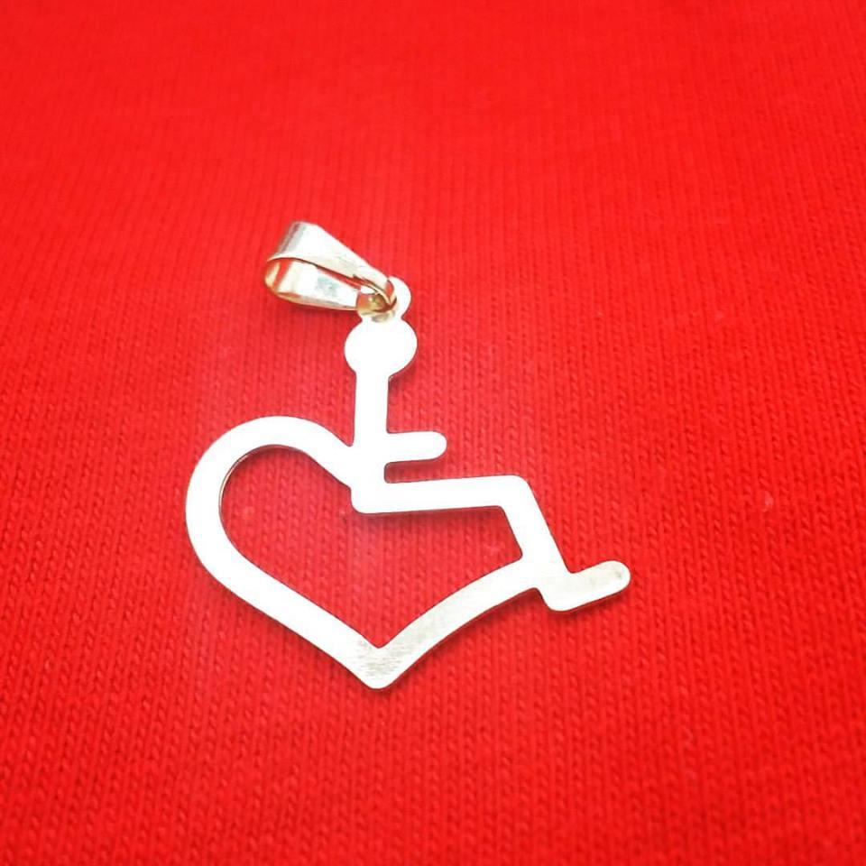 Pingente em formato metade cadeirante, metade coração, banhado a ouro No fundo uma tela vermelha
