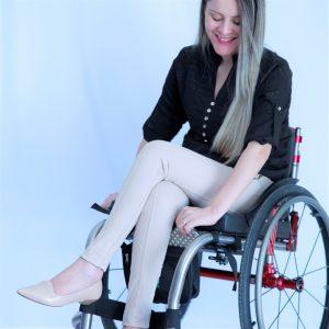 Foto ilustrativa da bolsa para a cadeira de rodas com uma mulher de pele clara, cabelos longos loiros, sorrindo, olhando para baixo enquanto insere um acessório na cor cinza e bolinhas brancas na bolsa, a modelo usa uma camisa de manga longa preta com botões no centro brancos, calça e sapato bege, com as pernas cruzadas, numa cadeira de rodas preta com detalhes em vermelho.