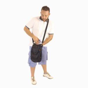 Imagem ilustrativa da bolsa na cor preta e detalhe laranja, na foto, um homem branco, cabelos curtos castanhos, barba, usa uma camisa branca com detalhes pretos e cinza nas mangas, short jeans azul, sapato na cor bege, o mesmo olha para baixo, inserindo um coletor de urina na bolsa.