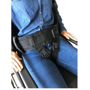 Foto ilustrativa em zoom, visão frontal da Cinta de transferência abdominal com alças laterais na cor preta, na imagem a modelo está sentada na cadeira de rodas de cor preta com as mãos de pele clara apoiadas a cadeira, usa a cinta na cintura e um conjunto de blusa e calça jeans azul.