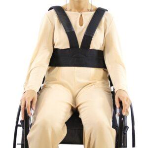 """Cinto DE SEGURANÇA para cadeirantes colete peitoral em """"v"""", na cor preta, na foto em questão, temos uma modelo BRANCA cadeirante demonstrada do joelho ao pescoço Numa cadeira de rodas preta, USA UM CONJUNTO BEGE, com as mãos apoiadas na cadeira, visão frontal."""