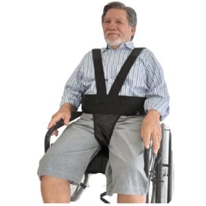 """Foto de um senhor idoso usando o cinto usando o cinto para a cadeira de rodas colete peitoral e pélvico Em """"v"""" , na cor preta e em detalhe a logo da reapta em laranja, o modelo sorri para a foto, homem branco, cabelos grisalhos e barba branca, usa uma camiseta com listras azuis, com um short cinza, o mesmo apoia as mãos na cadeira."""
