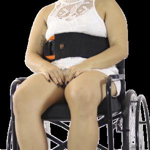 Visão frontal do cinto para a cadeira de rodas em velcro na cor preta e detalhes laranja, zoom numa modelo em cadeiras de roda com as mãos apoiadas à sua frente do pescoço à panturrilha, no modelo de pele clara usando um conjunto na cor branca.