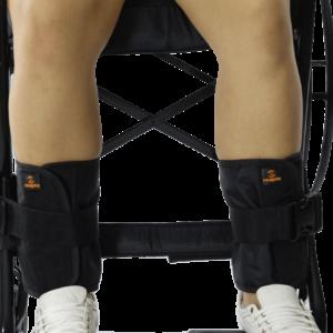 Foto ilustrativa do contensor de perna da reapta na cor preta com a logo laranja, em zoom duas pernas de pele clara, tênis brancos e ao fundo detalhes em preto de uma cadeira de rodas.