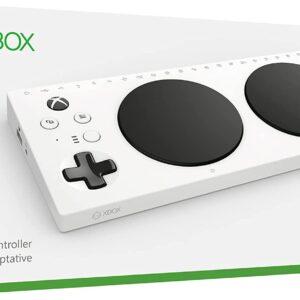 """Imagem do produto controle adaptável xbox da Microsoft, dispositivo branco, com 2 grandes botões pretos e na esquerda mais botões em preto e branco de atalhos, produto em uma caixa branca com a logo em verde do xbox e abaixo em inglês os nomes: """"adaptive controller, manette adaptive"""""""
