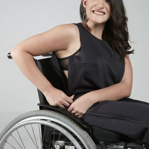 Imagem de uma modelo em cadeira de rodas, mulher branca, cabelos castanhos sorrindo, usando abertura lateral da regata em zíper, com uma calça preta.