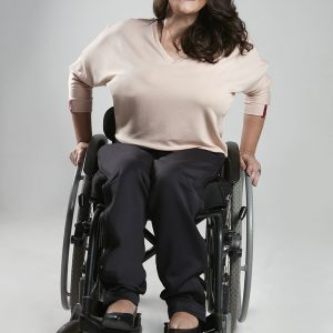 Imagem de uma modelo cadeirante, mulher de pele clara, cabelos castanhos longos, sorri com os braços apoiados na cadeira, usa uma blusa Fly de manga longa e decote em v na cor bege, calça e sapatos pretos, no fundo cinza.