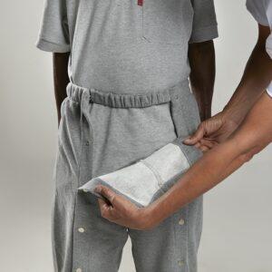 Imagem ilustrativa em foco na calça moletom de abertura frontal assessorada por uma segunda pessoa de jaleco branco simulando a abertura em um modelo em pé.
