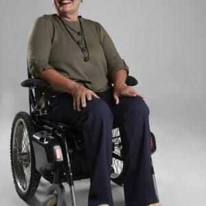 Modelo cadeirante, mulher de pele branca cabelos curtos e grisalhos sorrindo com as mãos apoiadas sobre os joelhos, usando uma camisa de manga longa na cor caqui, colar preto com bolinhas, com uma calça azul sapatos na cor bege.